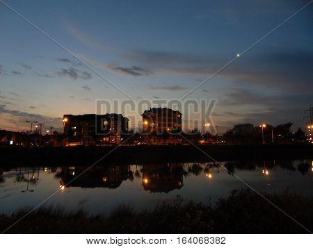 hermoso atardecer en hualpen, con edificios reflejados en estero y la luna alumbrando la ciudad