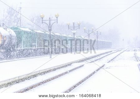 Blizzard on railway freight train in snow and traffic lights behind