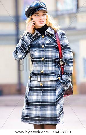 Mooie jonge blond in een vacht gesprekken op telefoon. Fotografie voor mode merk catalogus kleding