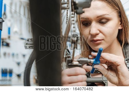 The edge of the repairing. Concentrated athletic skillful technician standing in the garage and working while mending the pedal of the bicycle