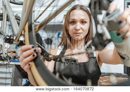 Paying attention to every detail. Athletic serious skilled craftswoman standing in the workshop near the bicycle and working while repairing it