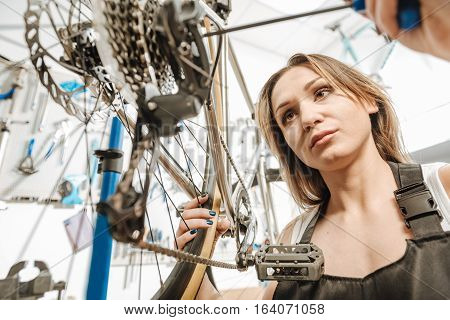 High quality specialist. Athletic involved skillful master standing in the repair shop near the bicycle and working while repairing it and holding the screwdriver