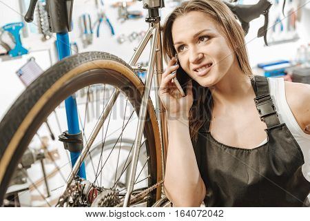 Pleasant conversation at work. Delighted cheerful young craftswoman standing in the repair shop near the bicycle and relaxing while talking over the phone and smiling