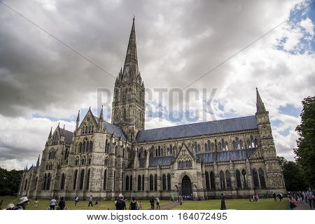 SALISBURY - JULY 17: the famous view of the Cathedral and park on sunny and cloudy day on July 17 2015 in Salisbury in South England