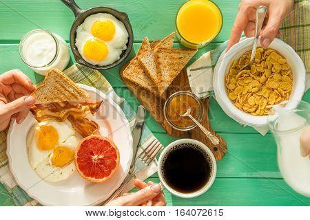 Family having summer breakfast, hands, top view