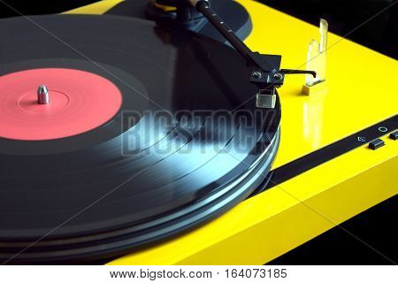 Vintage vinyl LP record with red label sound reproduction on vintage turntable record player with yellow case isolated on black background. Horizontal photo diagonal view closeup