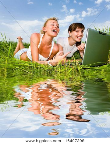 Two beautiful girls in white clothes are laughing and looking at laptop computer outdoors. Lay on the green grass. Reflected in water