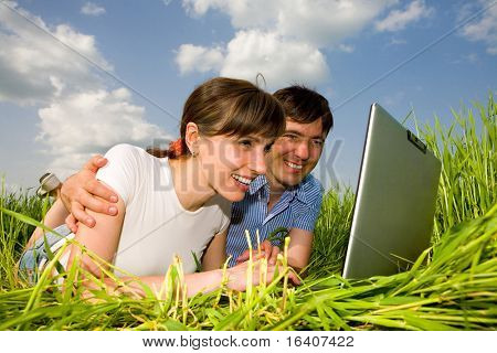 Happy couple on a laptop computer outdoors. Lay on the green grass.