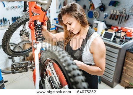 Involved diligent female master standing in the repair shop and working while repairing the mountain bicycle and expressing joy.
