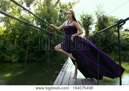 Young Beauty Girl In Fluttering Lilac Dress Standing Alone On The Bridge In Summer Of Sunny Day, Out