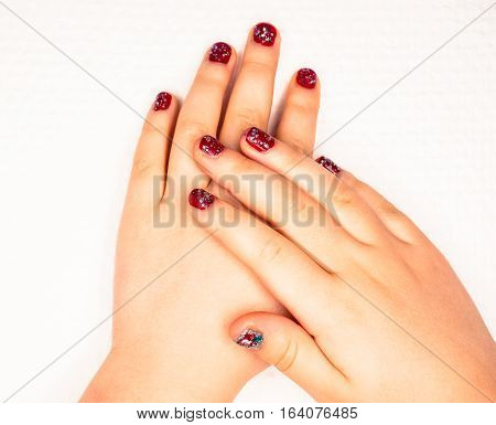 Little girl with beautiful manicure in dark pink towards white paper