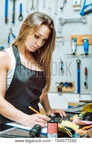 Keeping tabs on instruments. Pleasant concentrated muscular craftswoman standing near the table in the workshop and keeping tabs on instruments while holding the pencil and writing
