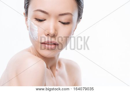 Skin care. Nice young Chinese woman looking down and having some cream on her cheek while standing against the white background