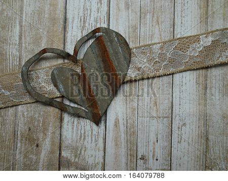 Wooden panels along with a lace and burlap ribbon provide the background for a large corrugated metal heart creating a rustic approach to love, friendship, and Valentine's Day.  Copy space.