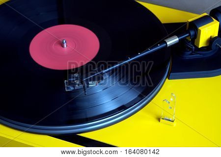 Turntable in yellow case playing a vinyl record with red label. Horizontal photo closeup