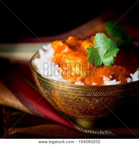 Bowl of spicy indian butter chicken in white basmati rice.