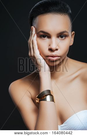 Look at me. Beautiful cute young woman wearing a bracelet and touching her cheek while looking at you