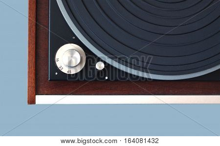 Part of vintage record player with wood finish top view isolated on cyan horizontal photo closeup