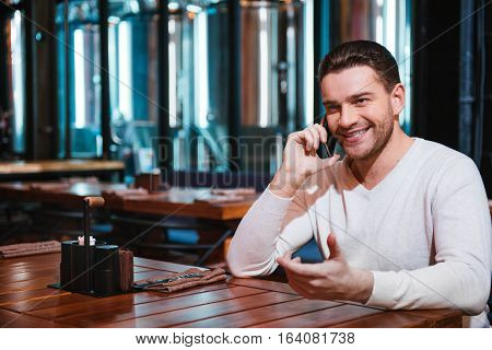 Modern technology. Positive happy brunette man putting his mobile phone to the ear and chatting with somebody while being in the pub