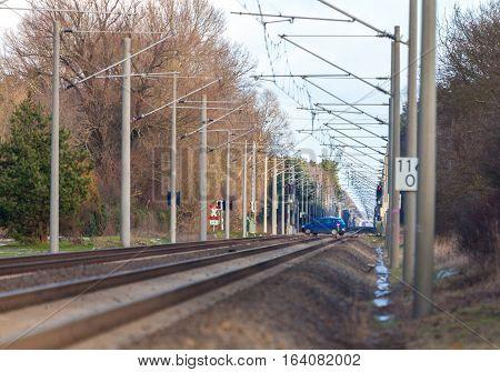 blue car drives over a railroad crossing