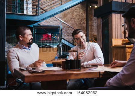 Friday evening. Pleasant nice handsome man sitting opposing his friend and pointing at him while spending time in the pub