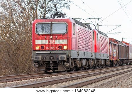 BURG / GERMANY - JANUARY 5 2017: german rail DB (Deutsche Bahn) Class 143 train with goods wagons drives on tracks.