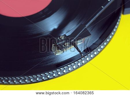 Vinyl LP record with red label sound reproduction on vintage turntable record player with yellow case. Horizontal photo closeup