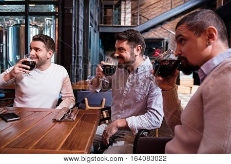 Great taste. Positive handsome delighted man holding glasses and taking sips of beer while watching football