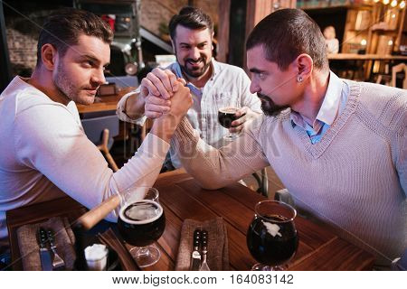 Entertainment for men. Handsome brutal strong men sitting at the table and confronting each other while arm wrestling.