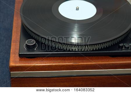 Part of vintage classic record player in wooden case with black LP vinyl record front view horizontal photo closeup