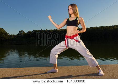 Karate girl practicing soto uke kata on lake near the water
