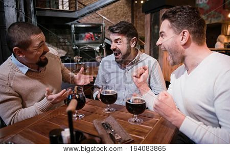 Positive emotions. Delighted happy male friends looking at each other and cheering about the victory of their football team while watching football in the pub