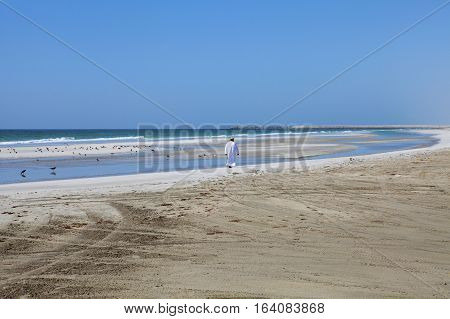 MIRBAT, OMAN - JANUARY 07,2016: Omani man walking along the beautiful Indian Ocean coast.