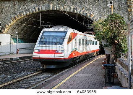 White passenger train driving out from tunnel near Vernazza town, Cinque Terre, Italy
