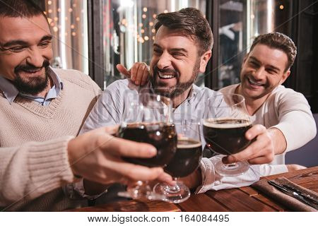 Alcoholic drinks. Joyful delighted handsome men laughing and clinking their glasses while drinking beer