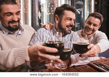 At the weekends. Happy positive male friends raising their glasses and cheering with them while meeting at the weekends in the pub