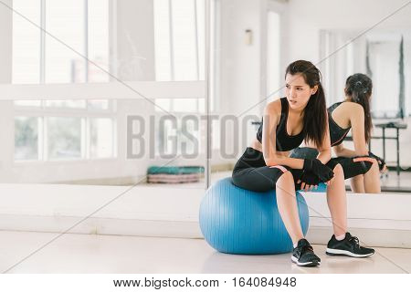 Young and determined sexy Asian girl on fitness ball at gym with copy space sport and healthy lifestyle concept
