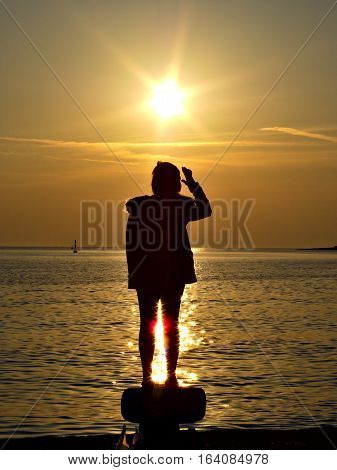 Silhouette of a woman standing on bollard at the harbor watching sea sunset.
