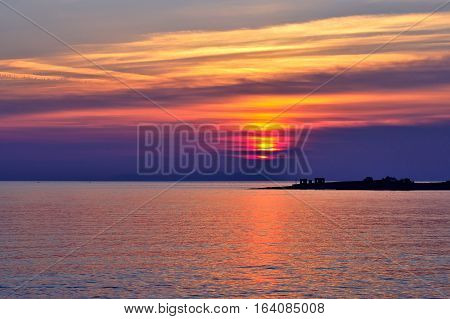Beautiful Aegean Sea sunset with vibrant clouds. Greek travel destinations poster.