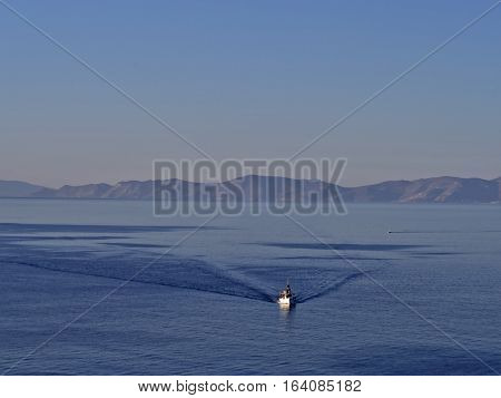Lonely white fishing boat in deep blue sea near Syros Island Greece.