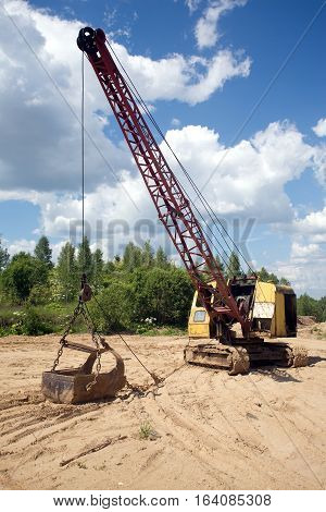 Yellow excavator with big heavy bucket standing on sand on background of forest and blue sky with white clouds on summer day vertical view