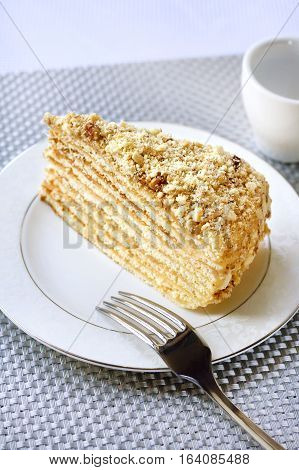 Piece of layer cake with custard and walnuts on a plate