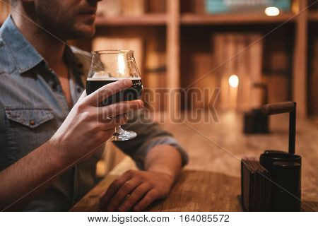 Wonderful drink. Close up of glass with beer being held by a handsome nice good looking man while sitting at the table