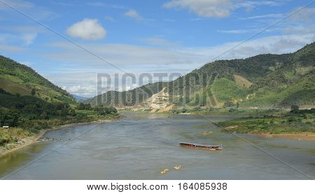 Travel laos boat in Khong river among mountain in border of Thailand and laos transportation and travel concept.