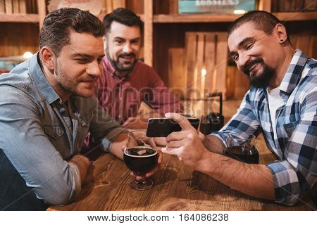 Showing something interesting. Positive nice bearded man holding his smartphone and showing something to his friends while enjoying his time with them