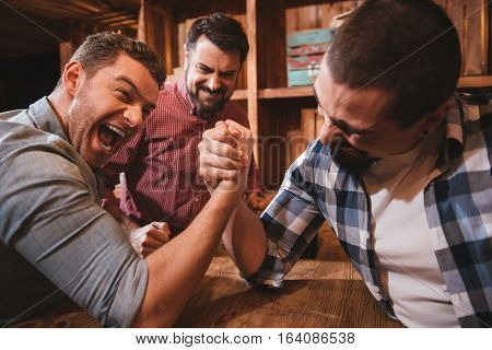 Armwrestling match. Good looking attractive brutal men holding their hands together and armwrestling while confronting each other