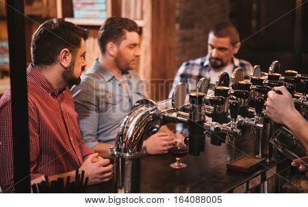Bar equipment. Selective focus of beer taps in the bar being used for pouring a drink with handsome positive nice men in the background