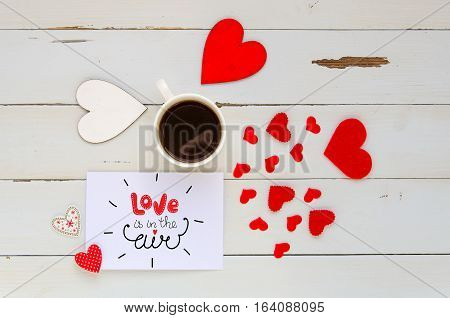 St Valentine's Day vintage overhead composition of note with love confession, hearts and coffee mug on wooden background