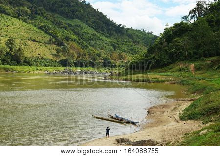 Beautiful river landscape. The khong river in mountains surrounded by greenery. Man on river bank takes photo of view.
