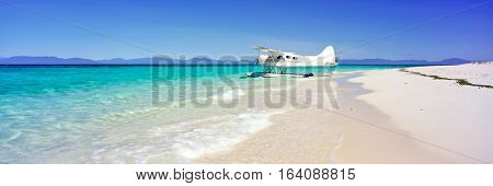 A seaplane on a sandy beach and blue water background